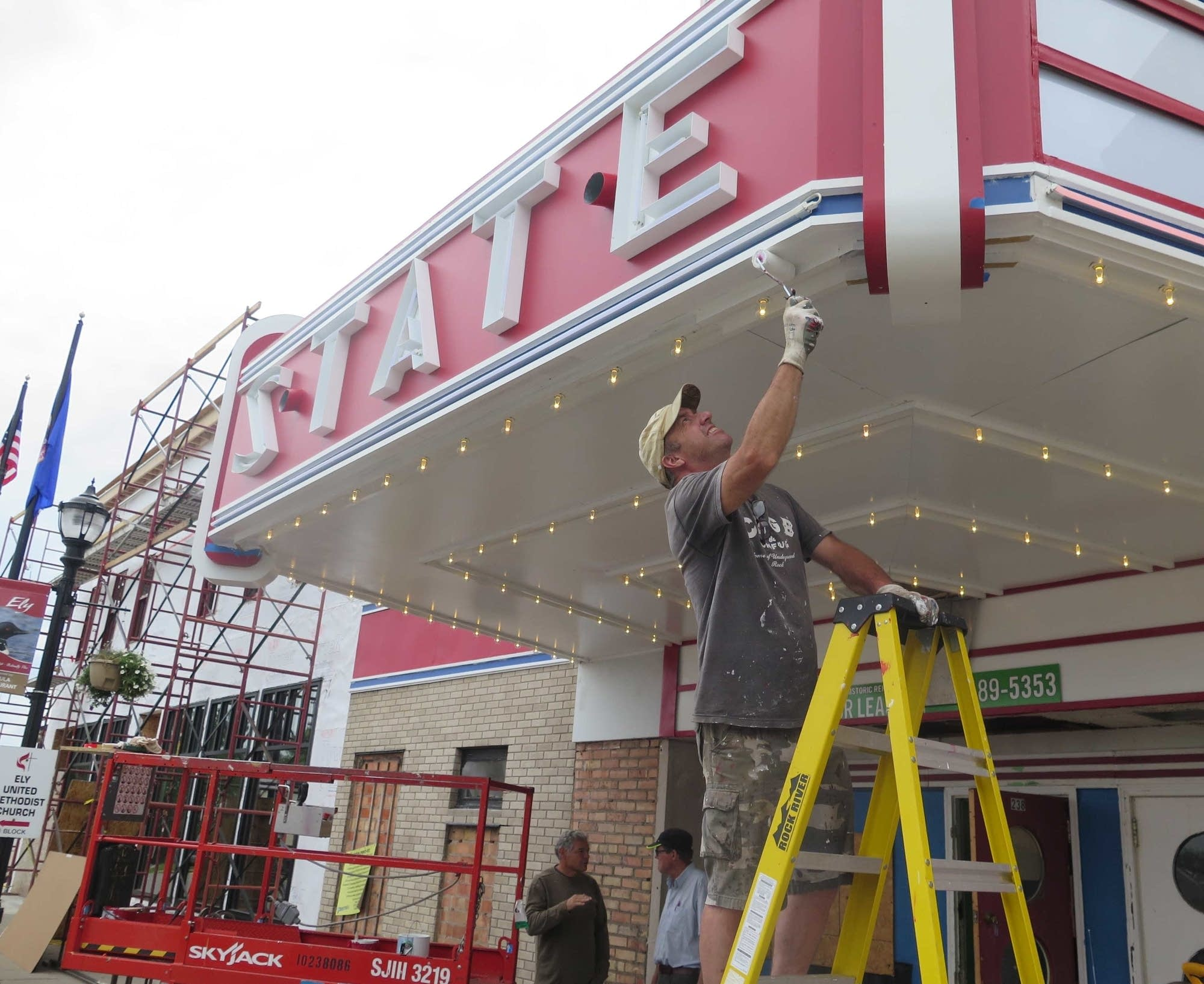Tom Quist paints the marquee of the State Theater