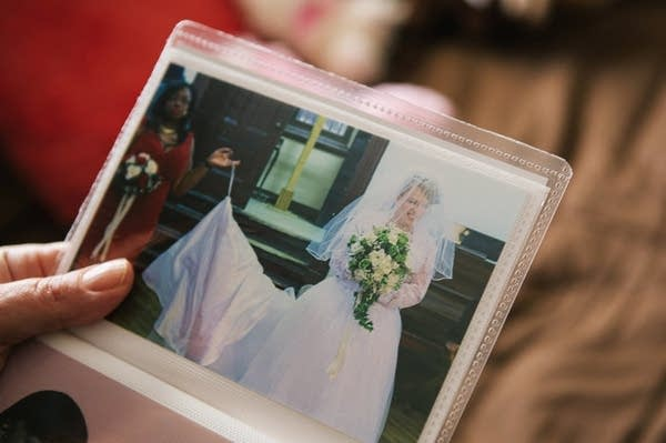 Pauline shows a photograph from her wedding day.