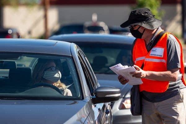 A man wearing a face mask talks to a person in a car.