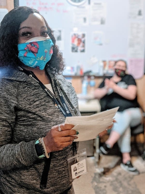 A woman stands wearing a surgical mask, holding paper