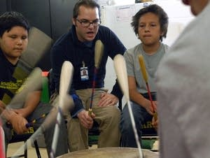 Teacher Ryan Bajan drums with students, including Kai Chavez, right.