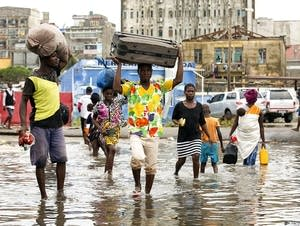 People carry personal effects after Tropical Cyclone Idai, in Mozambique.