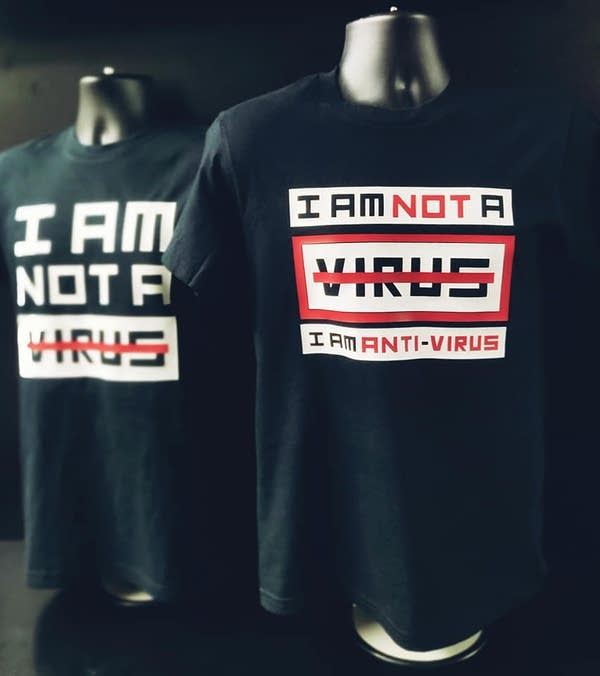 "Two black t-shirts on mannequins that read ""I AM NOT A VIRUS"""