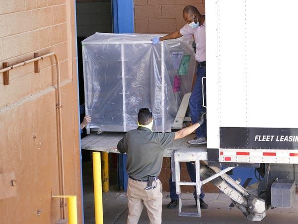 People unload election equipment