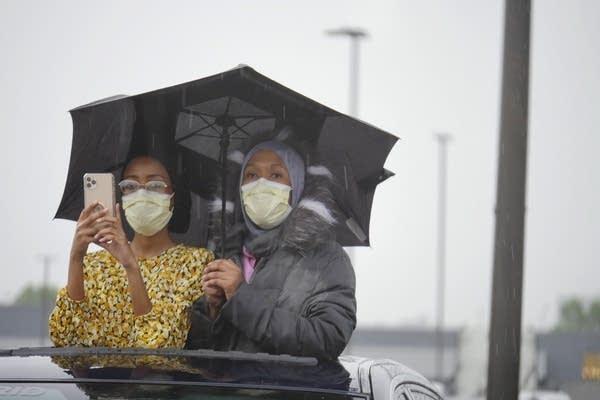 Two women wear face masks.