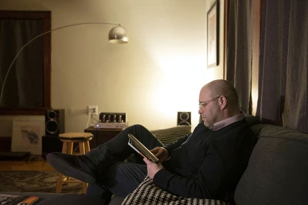 A man sitting on a gray couch reads a book.
