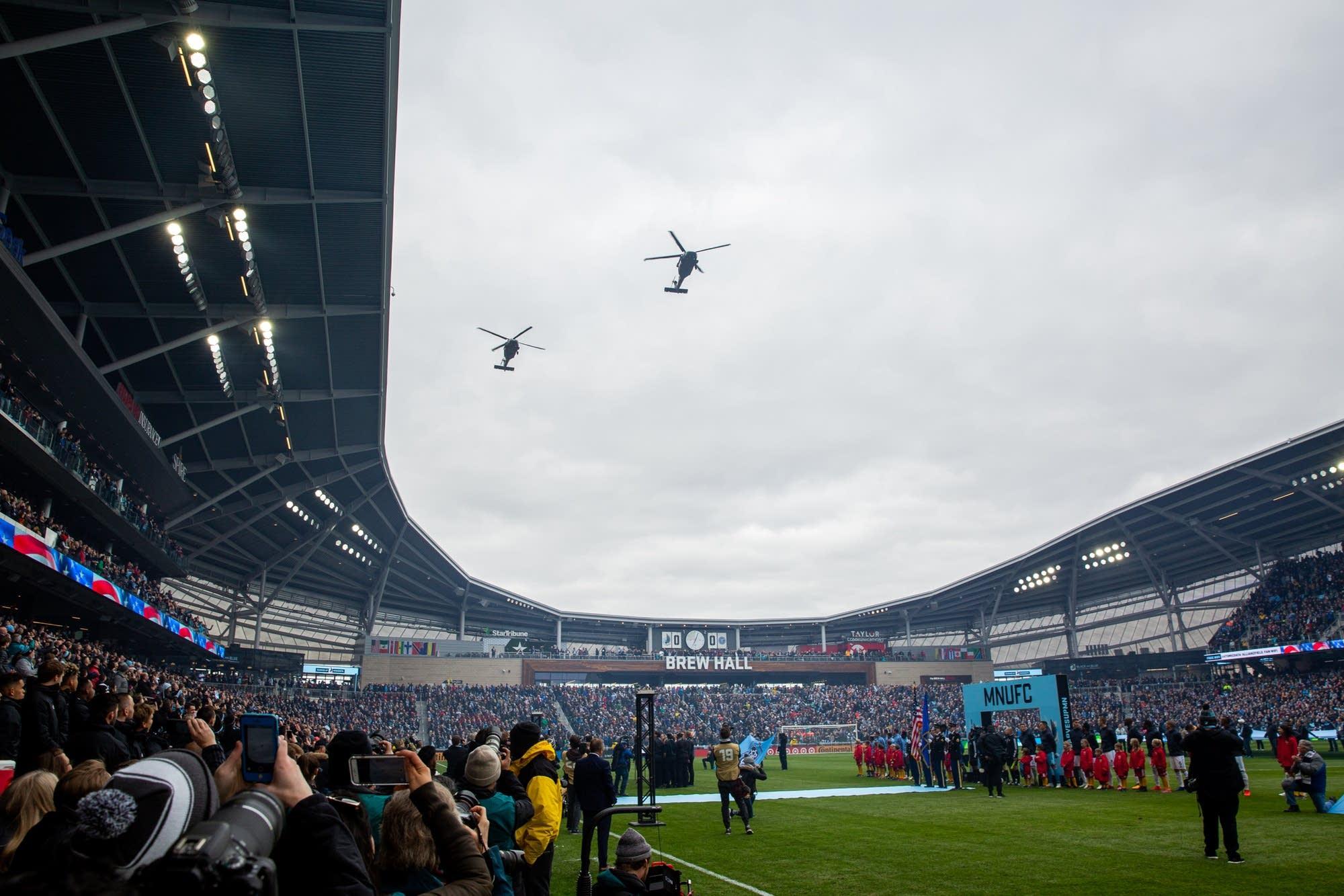 Military helicopters buzz Allianz Field.