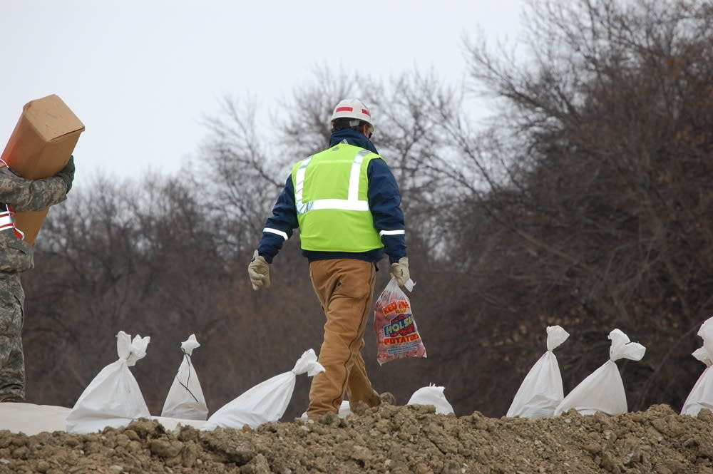 Worker hauls a bag of potatoes on top of the dike