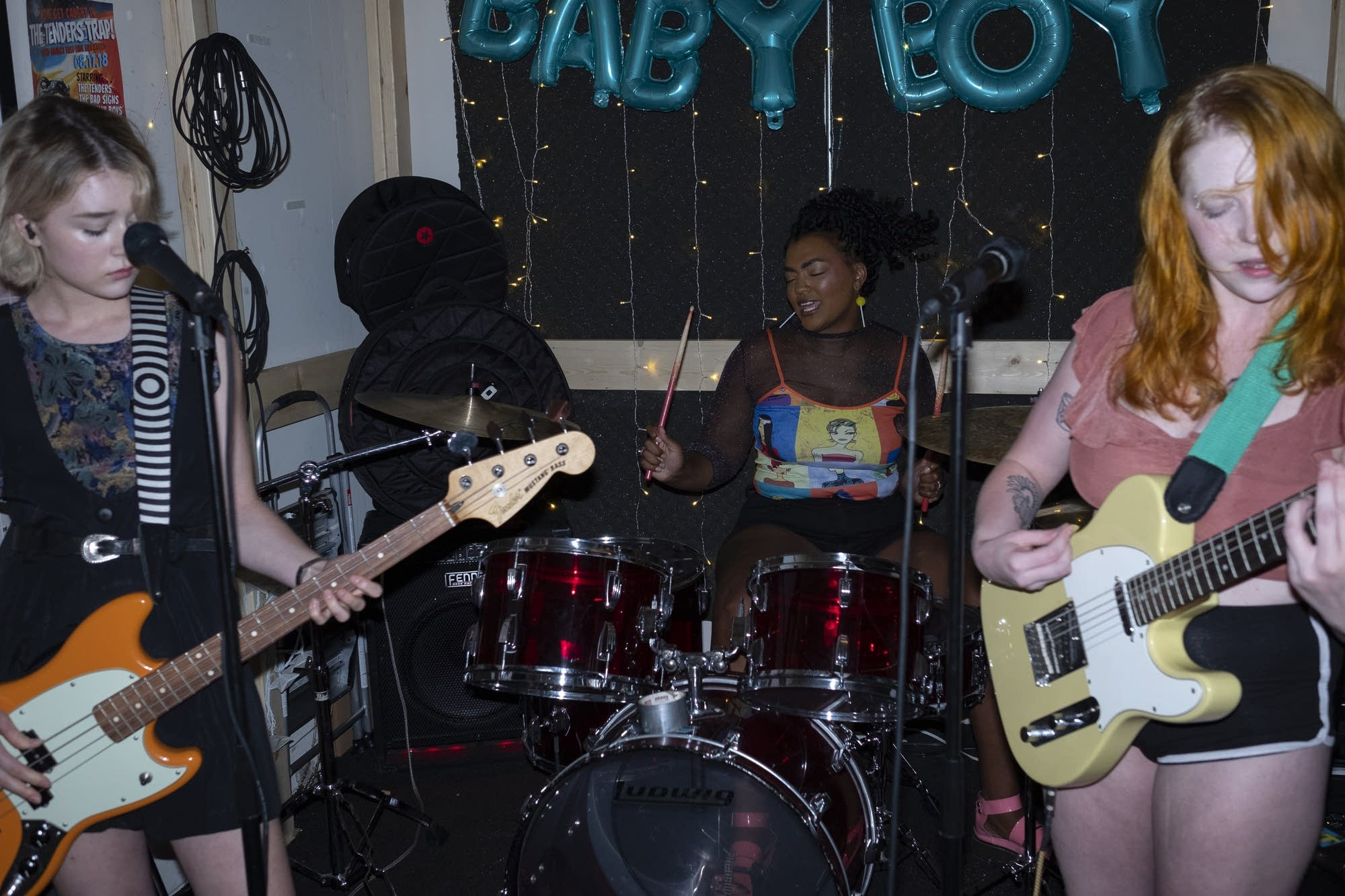 Three people in a band practice.
