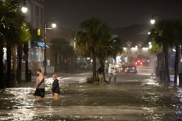 People walk through floodwaters.