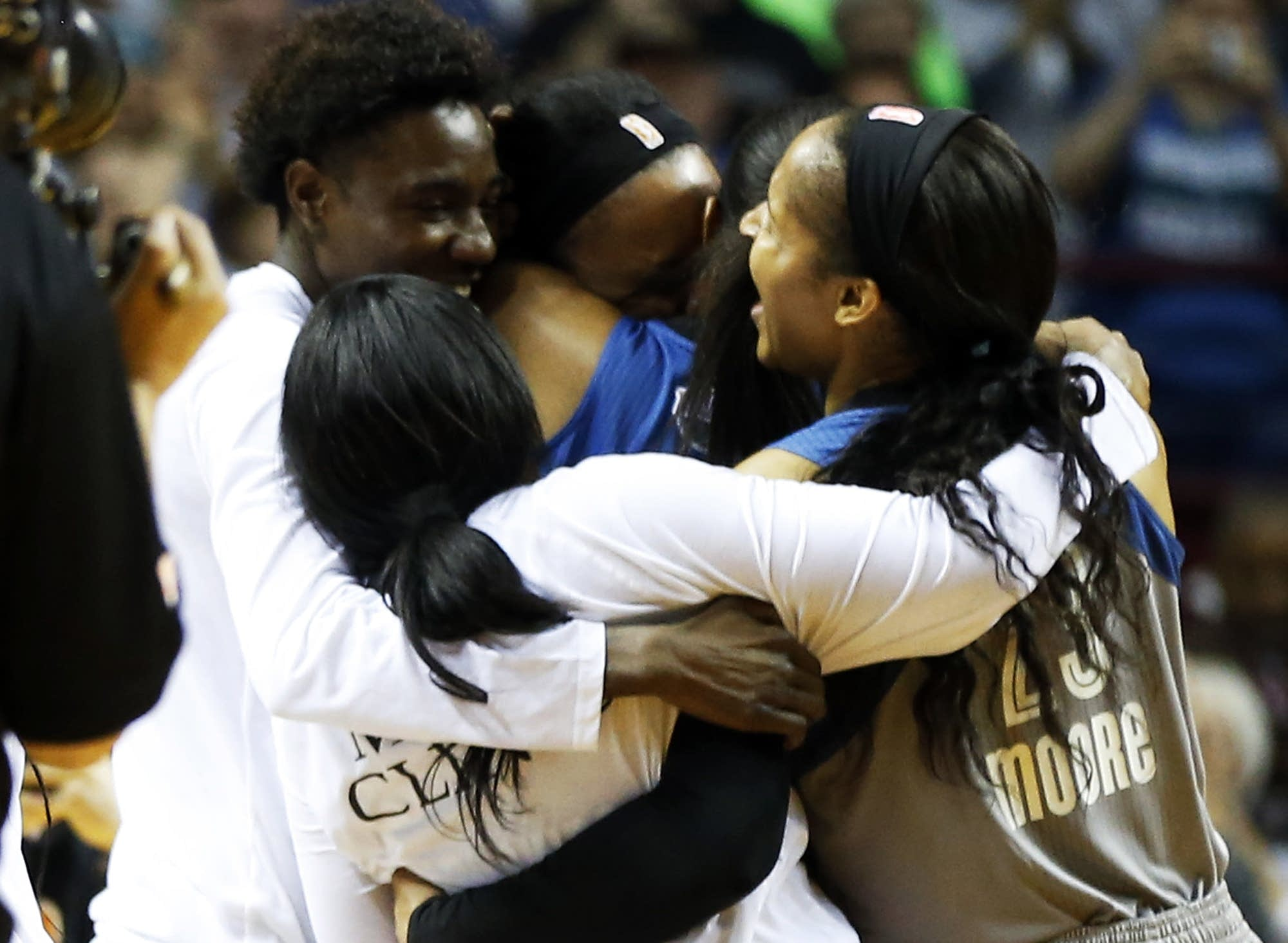 Maya Moore, right, and teammates celebrate after they win the championship.