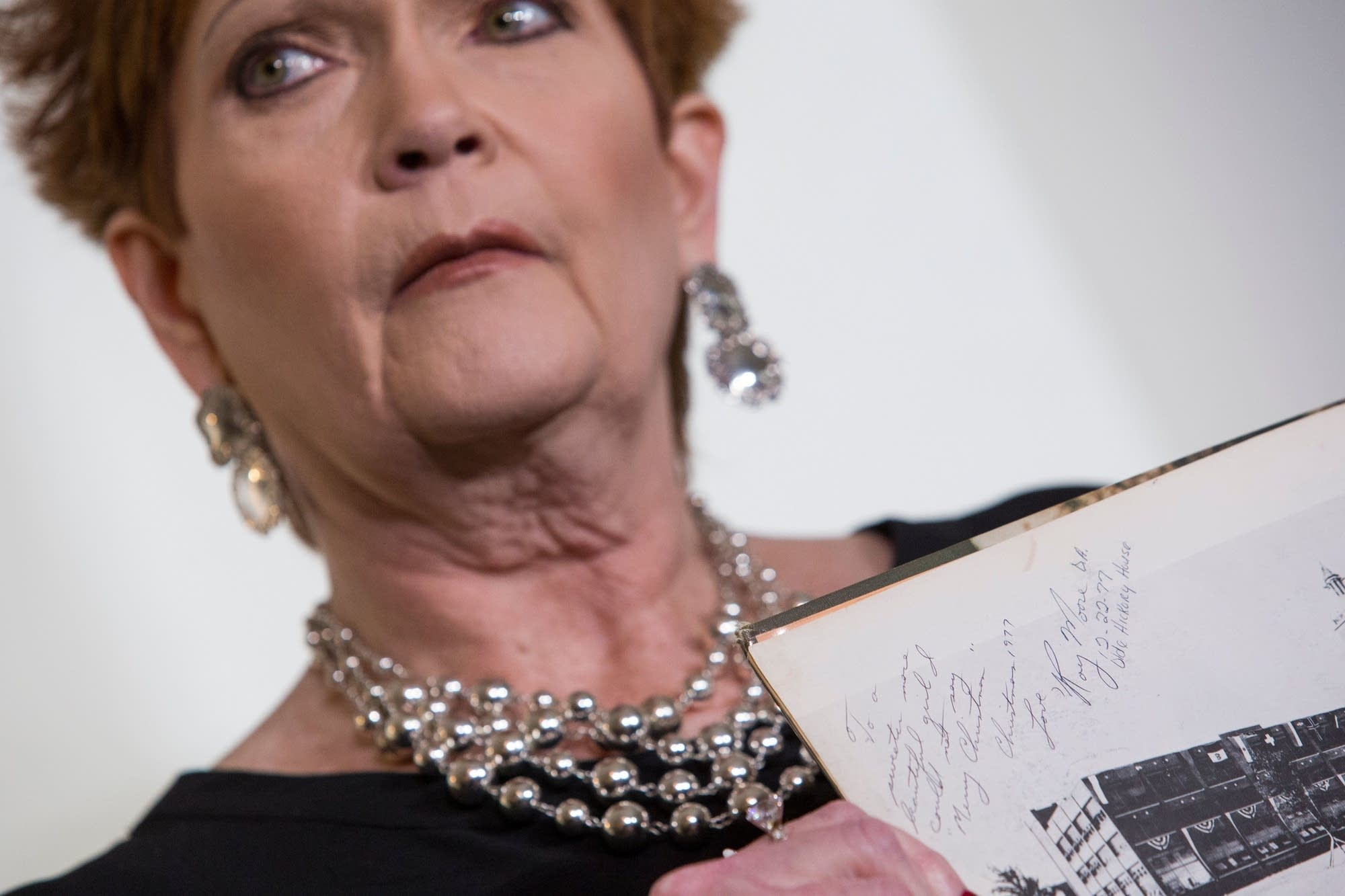 Beverly Young Nelson holds up a picture showing a message from Roy Moore.
