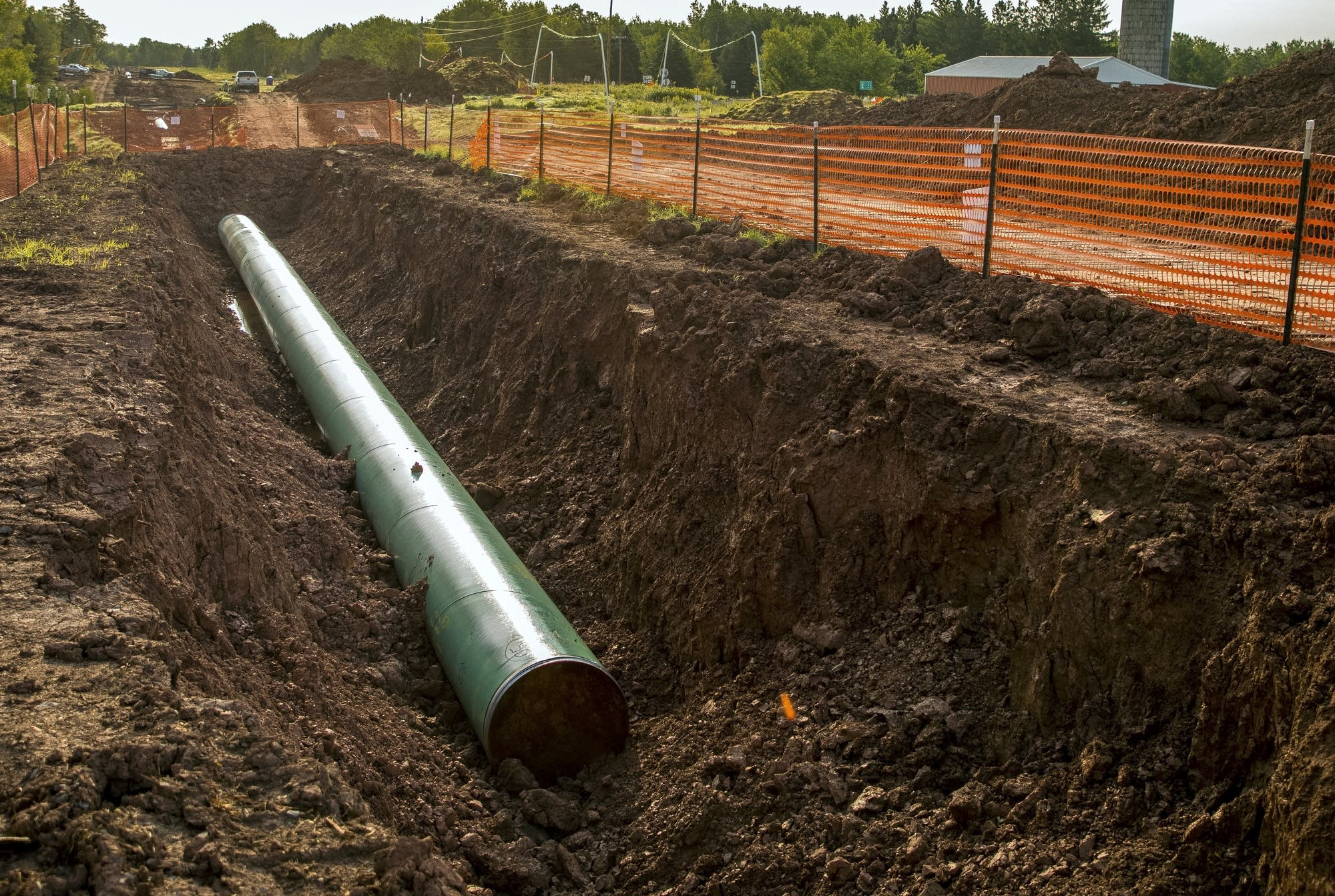 A new section of pipeline sits across the street from a farm.