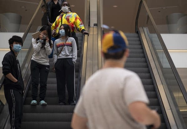 People wear masks on an escalator.