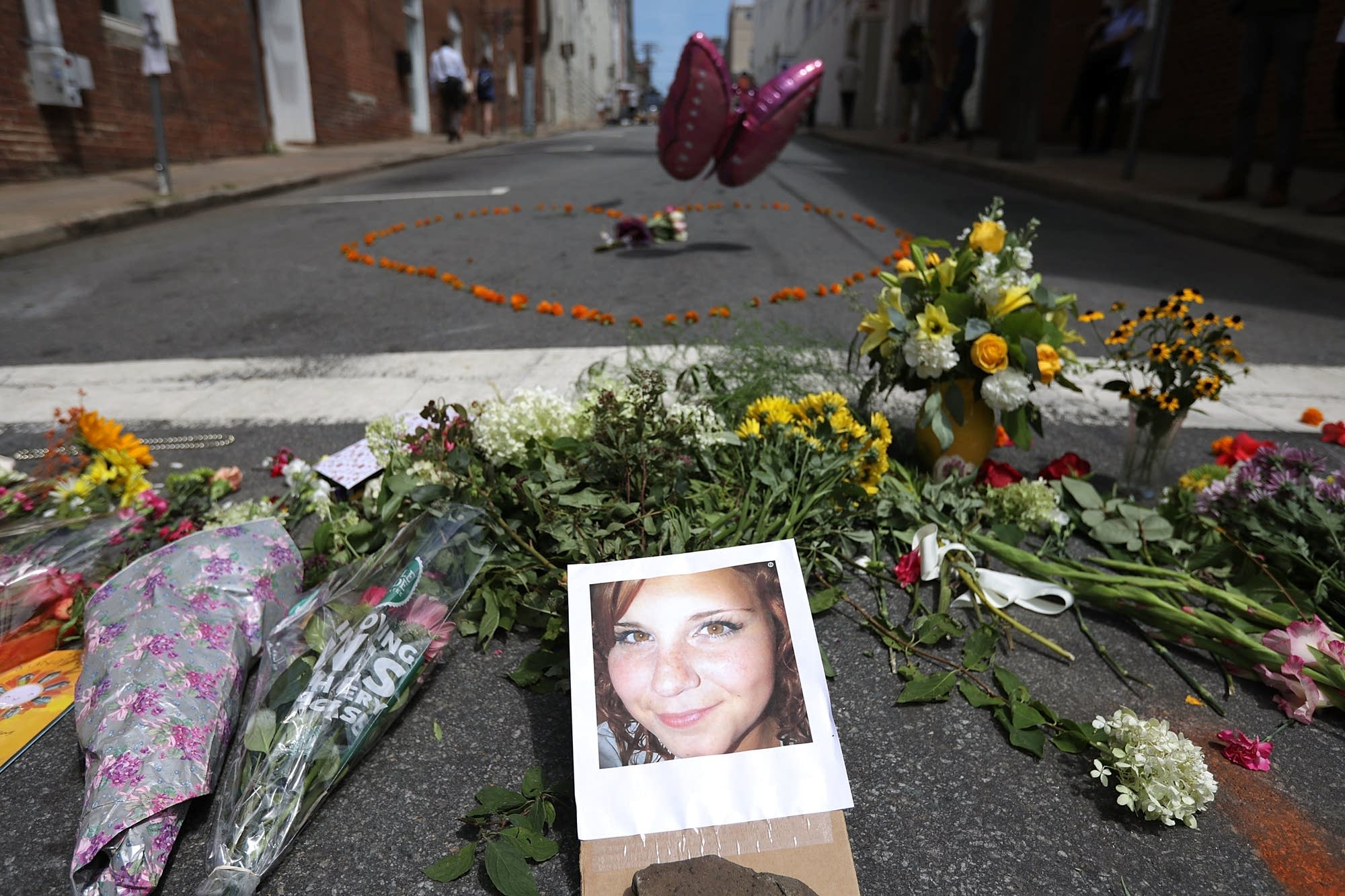 Flowers surround a photo of 32-year-old Heather Heyer.