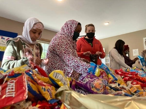 A group of people packs bags of candy.