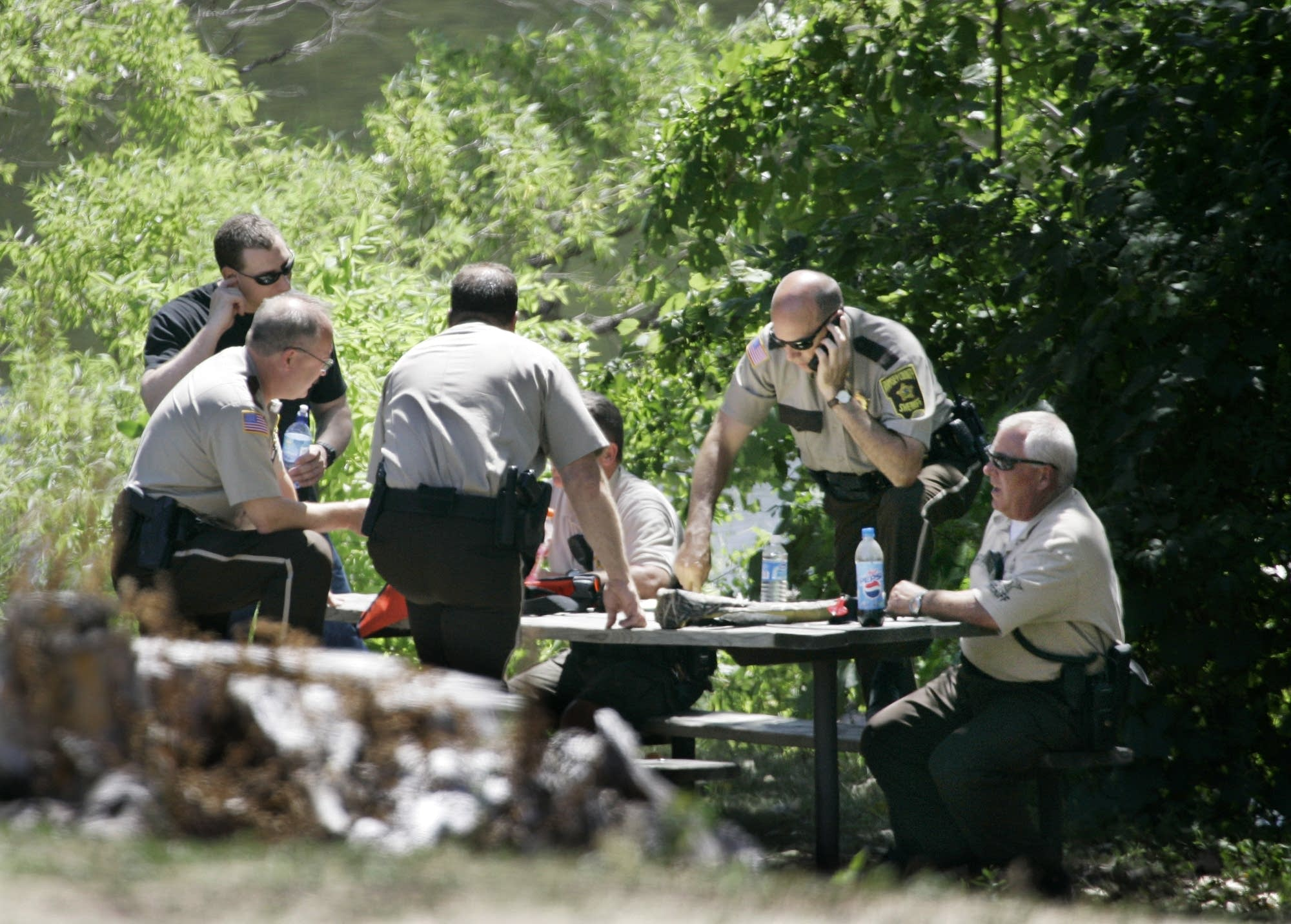 Local police officers meet over a picnic table.