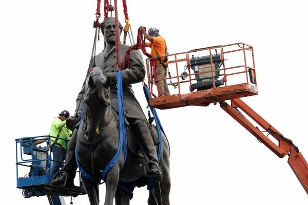 Workers tie up a statue prior to its removal from a pedestal.