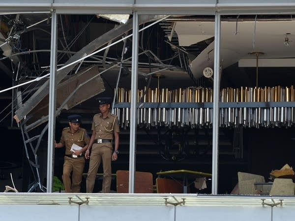 Sri Lankan police stand at the site of an explosion