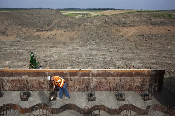 A construction worker works on building a large structure.