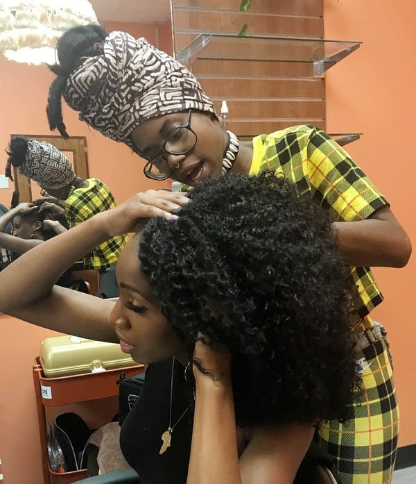 A woman touches holds her hands on head as another woman works on her hair