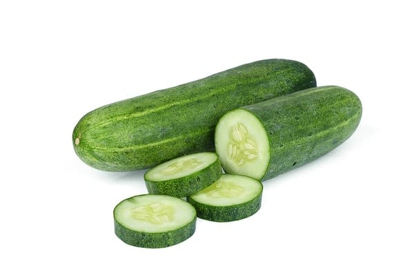 2 cucumbers (one of them partially sliced) on white background