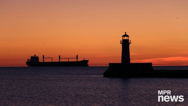 A ship and lighthouse on a lake at sunrise.