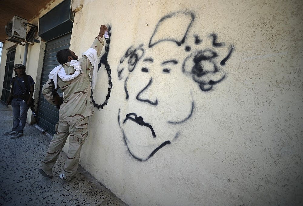 A rebel sprays graffiti depicting Col. M