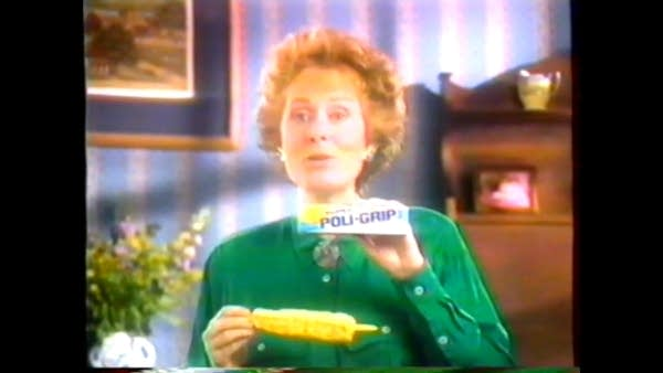 White woman on TV holding ear of corn and tube of Poligrip denture adhesive