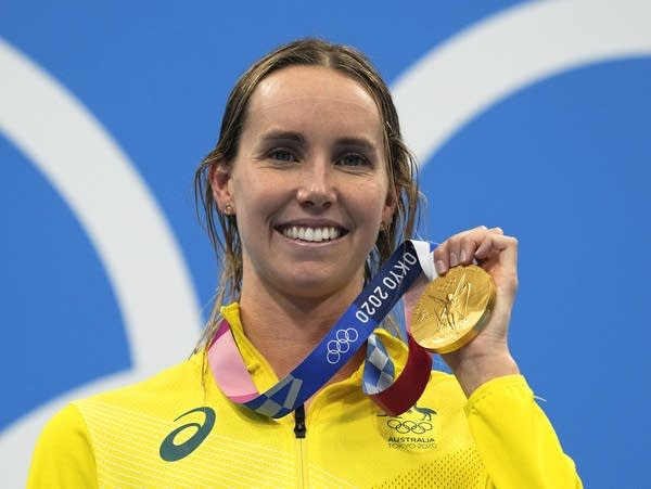 A swimmer poses with her Olympic gold medal