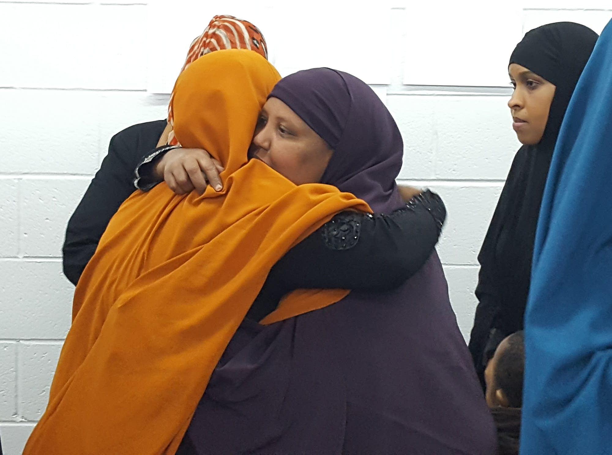 Ruun Abdi of Bloomington, in the dark purple, receives hugs.