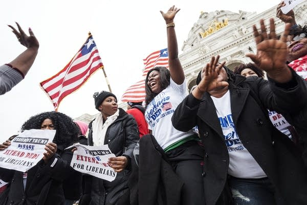 Evelyn Jarbah of Brooklyn Park, center, sings with the crowd at a rally.
