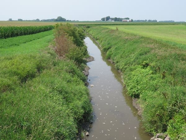 A drainage ditch cuts through a field