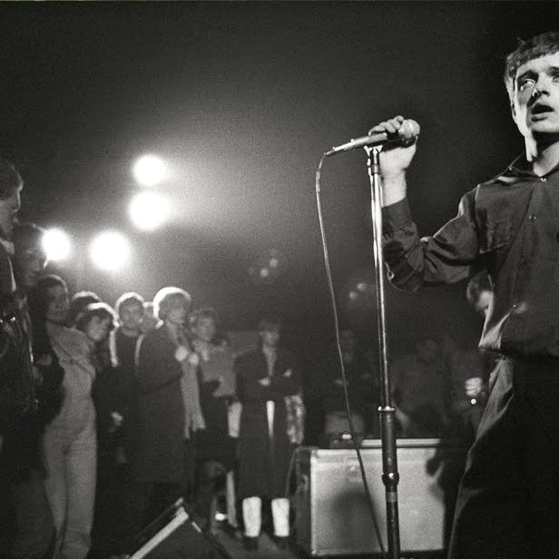 Ian Curtis on stage with Joy Division