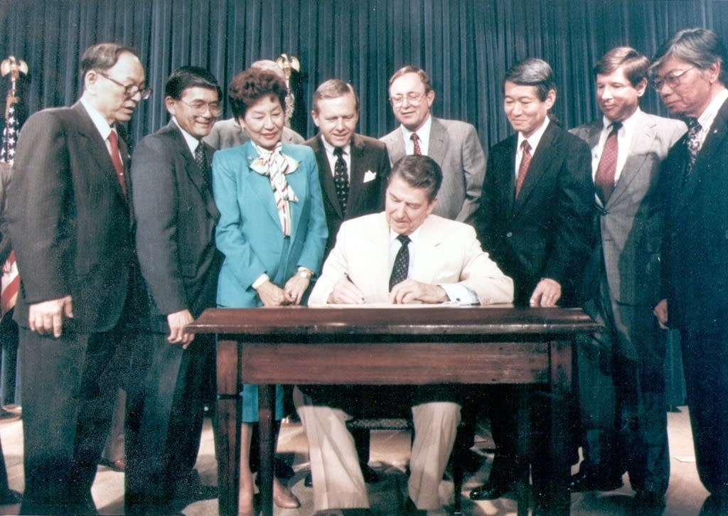 President Ronald Reagan signs the Civil Liberties Act of 1988