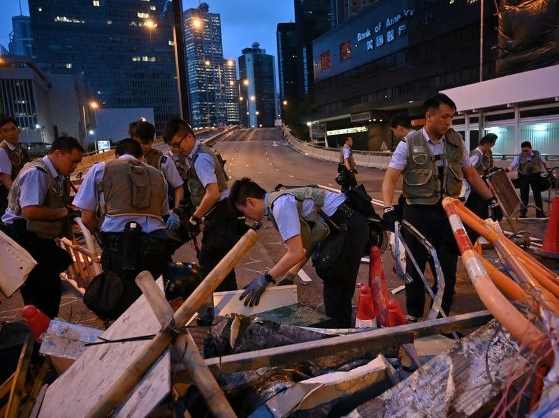 Police officers dismantle barricades placed earlier by demonstrators.