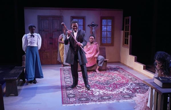 On a theater stage, four people of African descent stand in a living room
