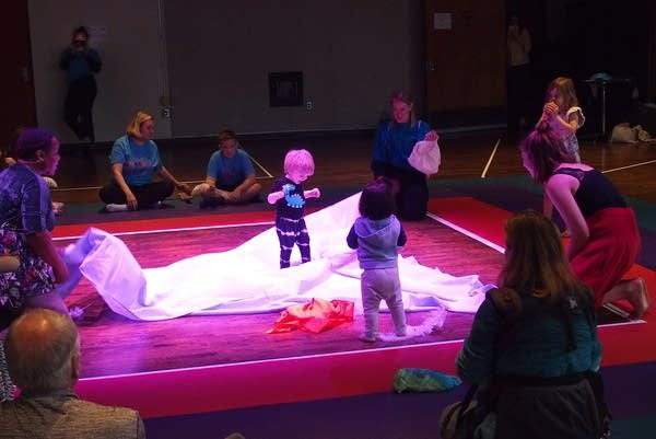 Singers unfold a sheet which will become a boat as a child climbs onboard.