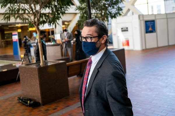 A man with a navy blue mask stands in a lobby.