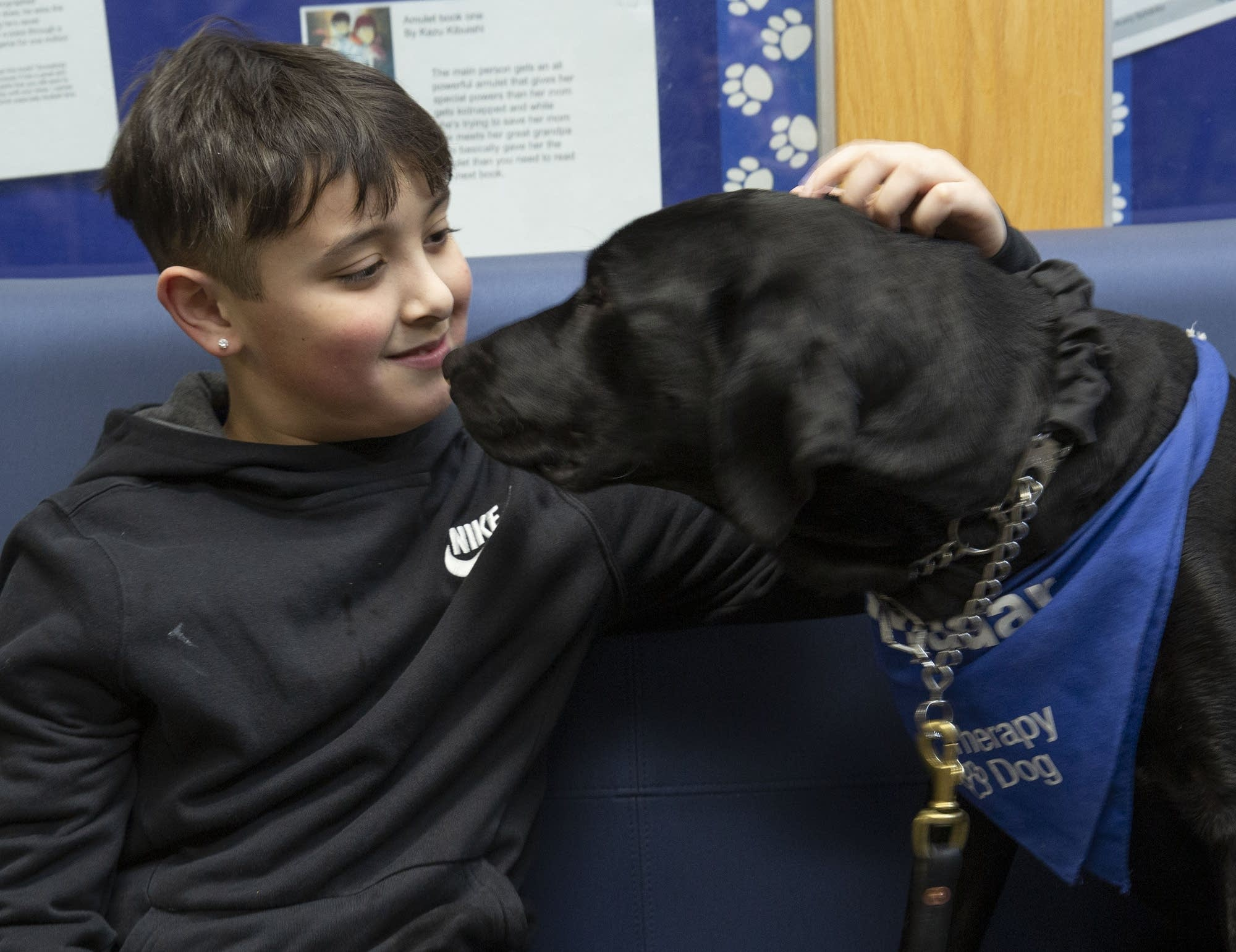 Oak Grove student Lucian Lally pets Radar during a stop in the hall.