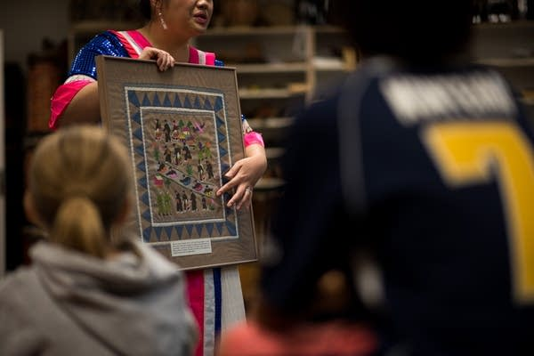 A story cloth depicts Hmong refugees fleeing Laos.