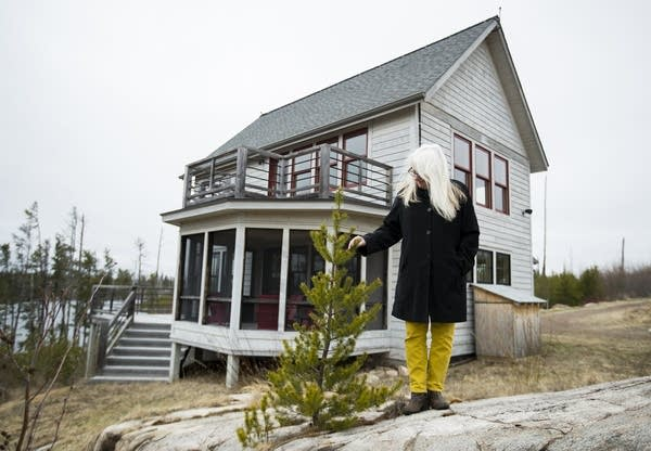 Jan Siverston stands in front of her new cabin, rebuilt after the fire.