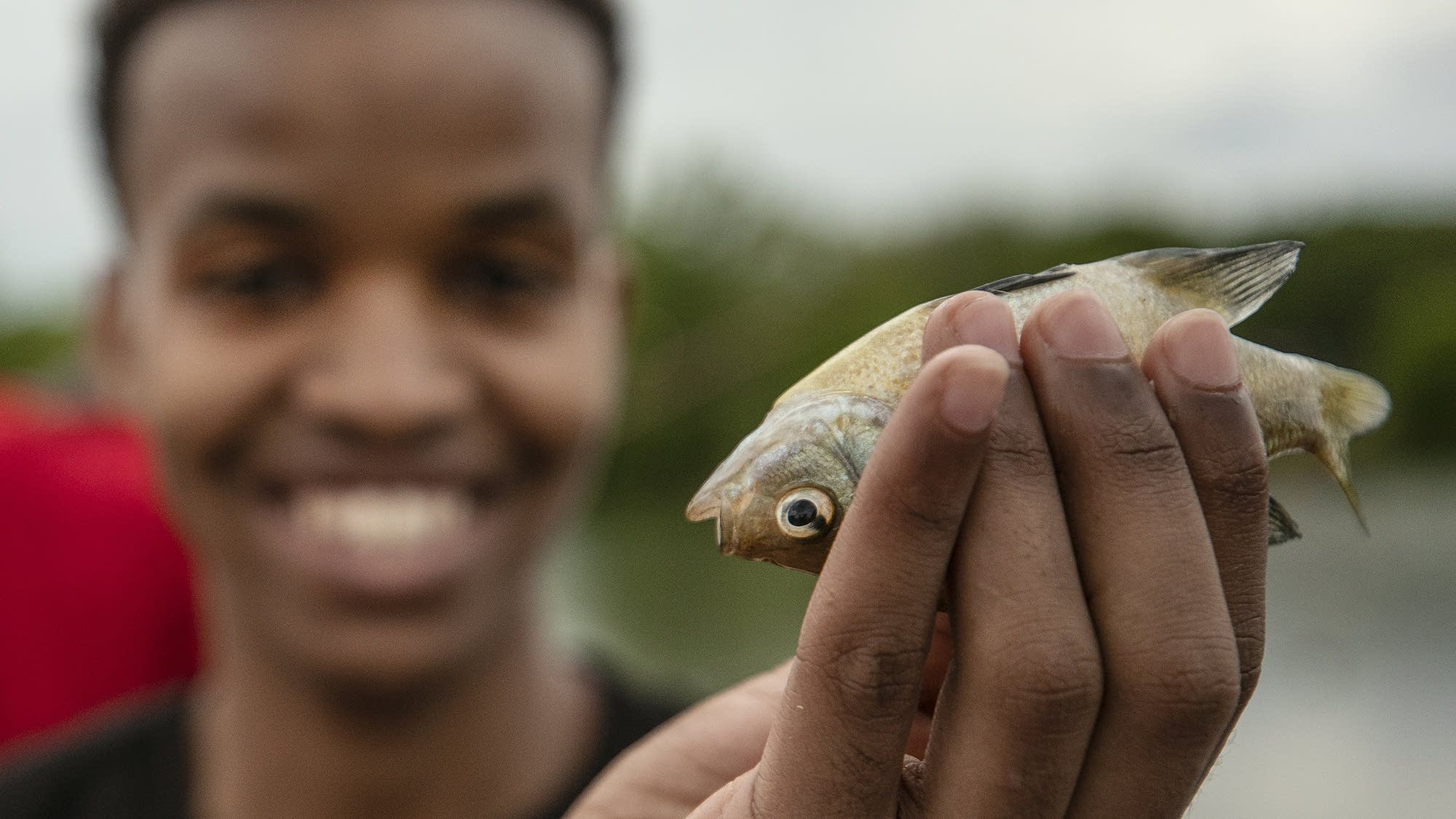 First-time fisherman Abdulahi Ahmed, 16, holds up a fish.