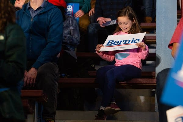 A young girl holds a Bernie sign.