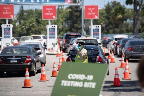 A traffic officer directs cars at a drive-thru COVID-19 test site.