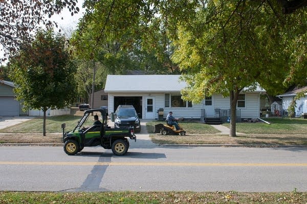 A person rides a John Deere gator in the street as person rides lawnmower