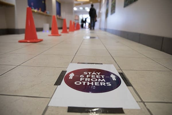 """A sign on the floor reads """"Stay 6 feet from others."""""""