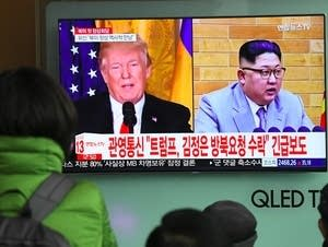 People watch a TV news report showing President Trump and Kim Jong Un.