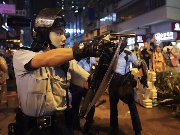 A police officer points a gun during a protest in Hong Kong