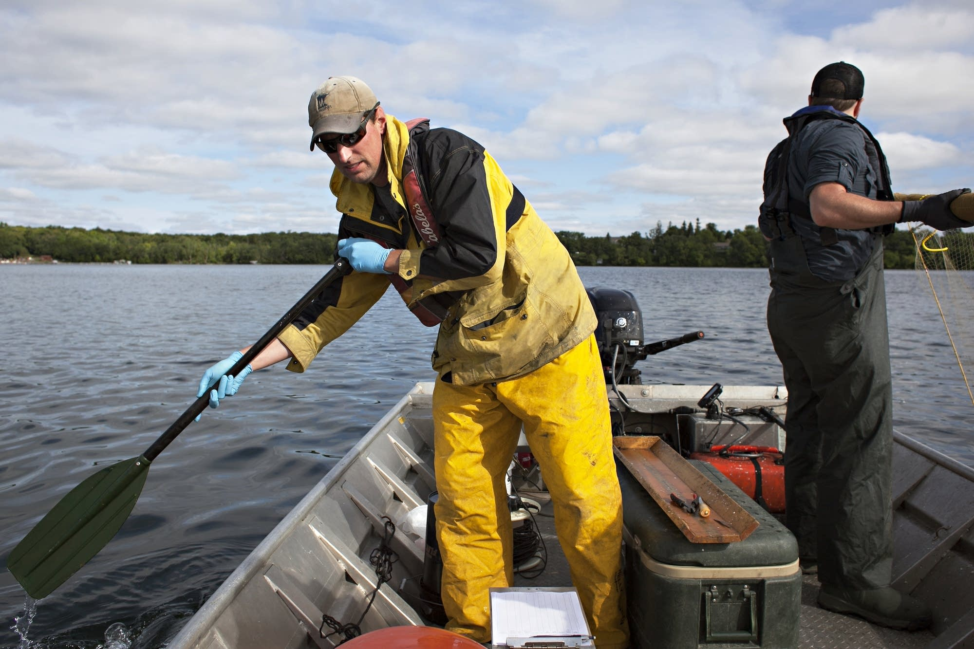 Biologist Will French, left, maneuvers a boat during a research outing.